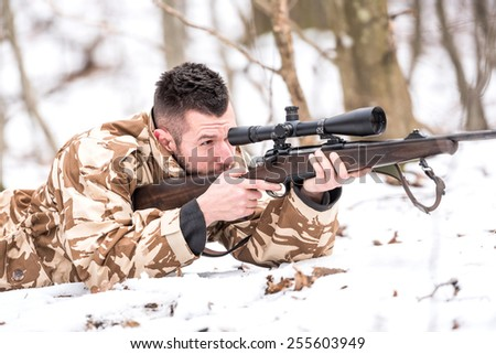 Hunter with a sniper rifle shooting during winter open season - stock photo