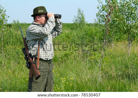 hunter with binoculars looking for venison - stock photo