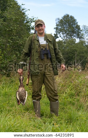 Hunter with duck in hand on a meadow. - stock photo