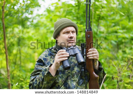 Hunter with optical rifle and binoculars in the woods - stock photo