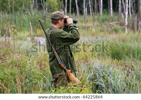 Hunter with rifle and binoculars in a forest`s swamp. - stock photo