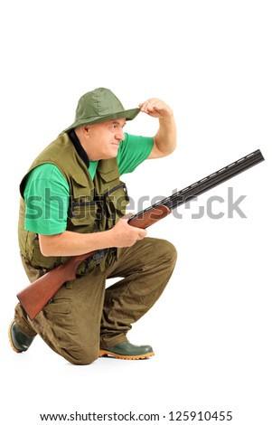 Hunter with rifle crouching and looking in the distance isolated on white background - stock photo