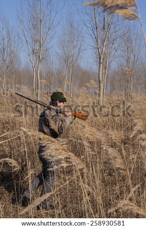 hunter with rifle looking for prey - stock photo