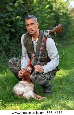 Hunter with shotgun and spaniel - stock photo