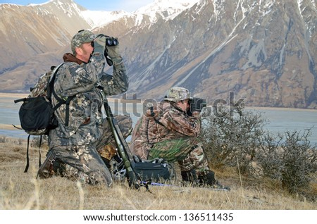 Hunters looking for Himalayan tahr in the Southern Alps of New Zealand - stock photo