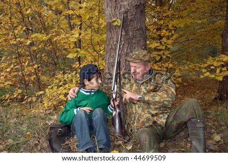Hunters with a gun. Grandfather and grandson talking under a tree in an autumn forest - stock photo