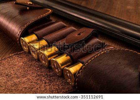 Hunting ammunition 12 gauge in leather bandolier and double-barreled shotgun on a wooden table. Focus on the cartridges - stock photo