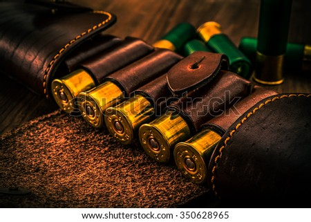 Hunting ammunition 12 gauge in leather bandolier on a wooden table. Focus on the cartridges, image vignetting and the orange-blue toning - stock photo