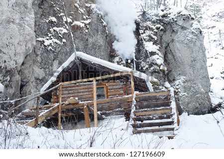 Hunting hut in the forest in winter - stock photo