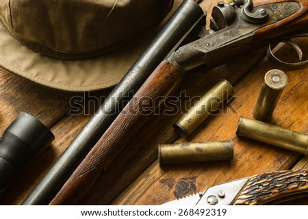 Hunting rifle, ammunition, a knife and a cap on the wooden table, close-up - stock photo