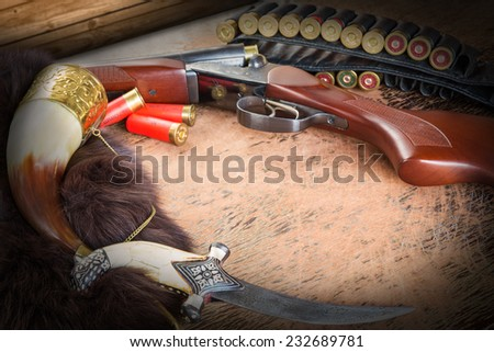 hunting rifle and dagger and amulet on the table. Image is colored  toned