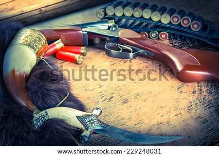hunting rifle and dagger  on the table. Image is colored  toned - stock photo