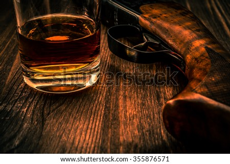 Hunting rifle and glass of whiskey close-up. Focus on the glass of whiskey, image vignetting and the orange-blue toning - stock photo