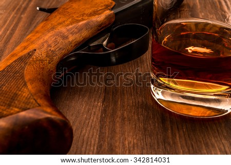 Hunting rifle and glass of whiskey close-up. Focus on the trigger of the rifle - stock photo