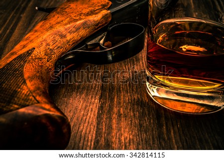 Hunting rifle and glass of whiskey close-up. Focus on the trigger of the rifle, image vignetting and the orange-blue toning - stock photo