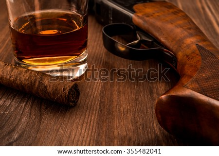 Hunting rifle and glass of whiskey with cuban cigar on the wooden table. Focus on the cuban cigar  - stock photo