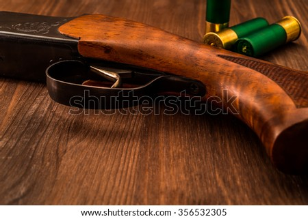 Hunting rifle with cartridges lying on a wooden table. Close up view - stock photo