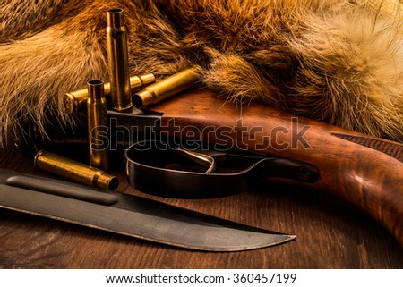 Hunting rifle with combat knife and empty shells lying next to the animal's fur produced. View close-up - stock photo