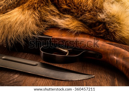 Hunting rifle with combat knife lying next to the animal's fur produced. View close-up - stock photo