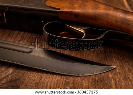 Hunting rifle with combat knife lying on a wooden table. View close-up - stock photo