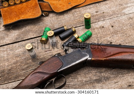 Hunting shotgun, ammunition on wooden background