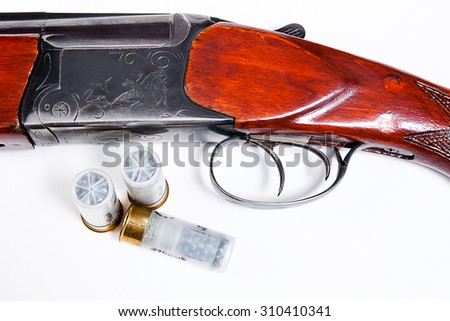 Hunting shotgun and ammunition on white background. Cartridges for hunting gun. Close up view showing mechanism of hunting rifle. Isolated on white. - stock photo