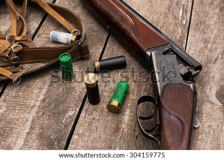 Hunting shotgun and ammunition on wooden background - stock photo