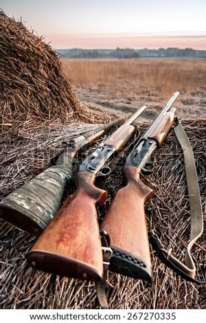 Hunting shotguns on haystack while halt during sunrise, soft focus on shotgun butt - stock photo