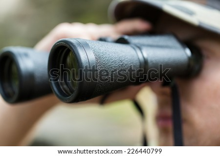 hunting, war, army and people concept - close up of young soldier, ranger or hunter with binocular observing forest - stock photo