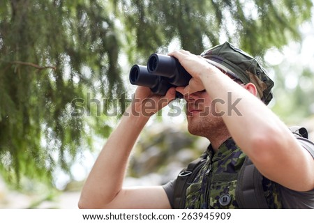 hunting, war, army and people concept - young soldier, ranger or hunter with binocular observing forest - stock photo