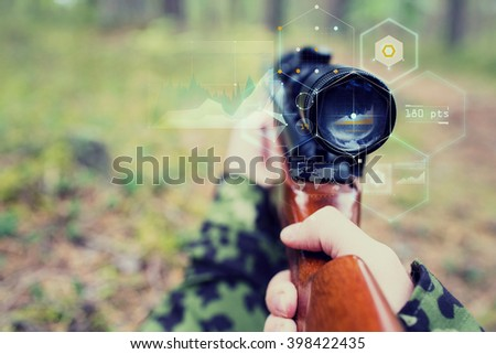 hunting, war, army, technology and people concept - close up of young soldier or sniper hands holding gun with virtual screen projection and aiming in forest - stock photo