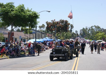 HUNTINGTON BEACH, CA - JULY 4: Military vehicle with people and American flag during Huntington Beach July 4th parade.