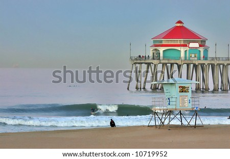 Huntington Beach Pier and Surfer at Dawn during Summer - stock photo