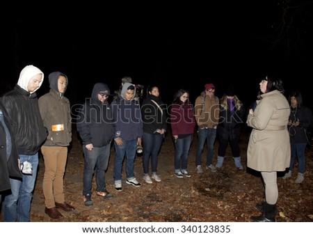 HUNTINGTON, NEW YORK, USA - NOVEMBER 14: Lindsay Klinger leads the Brooklyn Paranormal Society in meditation before investigation of Mount Misery Road in Long Island. Taken November 14, 2015 in NY. - stock photo