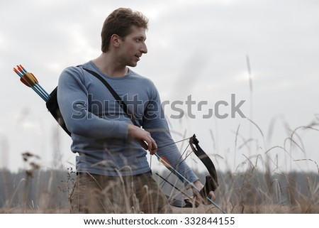 Huntsman charges bow in open air field. Autumn hunting.