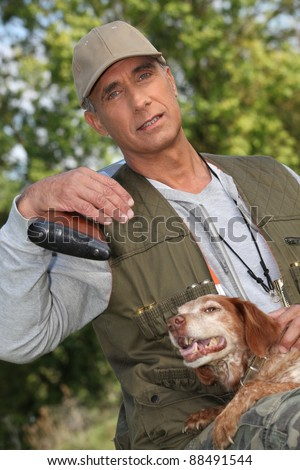 huntsman posing with dog outdoors - stock photo