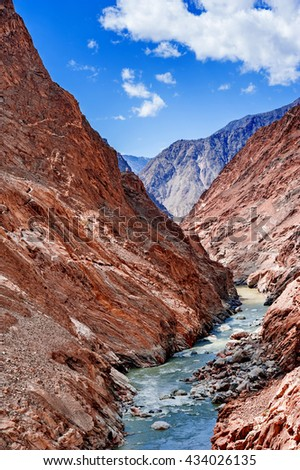 Hunza river flowing through the beautiful mountain valley in the northern part of the Karakorum mountains in Pakistan - stock photo