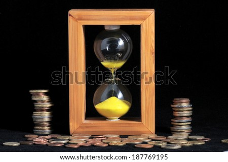 Huorglass and coins- Time is Money concept - stock photo