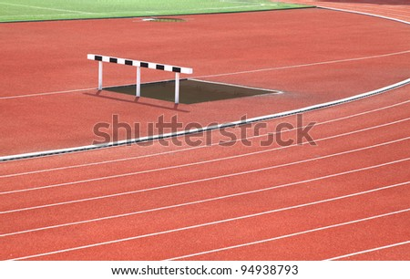 Hurdle and Curve of Race Track in Stadium - stock photo
