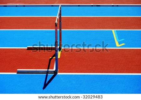 Hurdle on a striped athletic track - stock photo