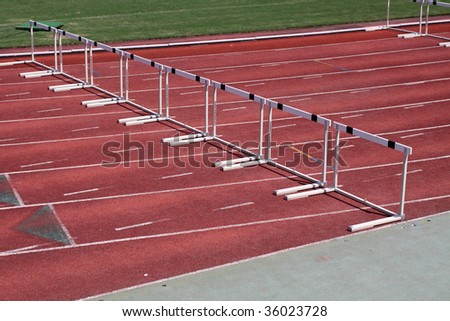 Hurdles in an empty track and field stadium - stock photo