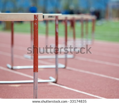 Hurdles lined up on a track, fading focus. - stock photo