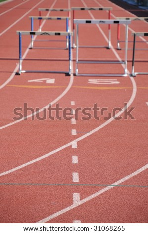 hurdles on a runners track with running lanes - stock photo