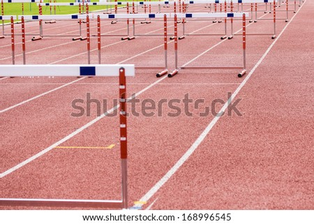 hurdles on the red running track - stock photo