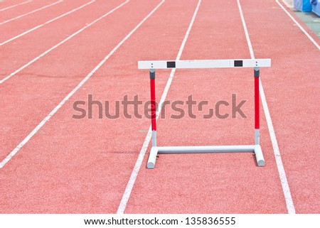 hurdles on the red running track prepared for competition. - stock photo