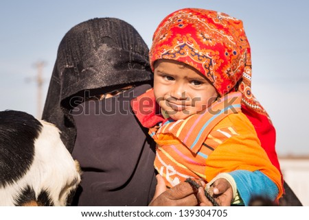 HURGHADA, EGYPT - APR 10: Unidentified arabic family with goat and donkey on the local bus station near Hurghada on 10 Apr 2013. This bus station is tourist attraction on the way to Luxor. - stock photo