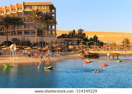 Hurghada, Egypt - Feb. 7, 2016: People enjoying the beach area with sun shades and lounging chairs at a resort on the Red Sea in Hurghada, Egypt