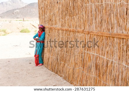 HURGHADA, EGYPT - MAY 18, 2015: Unidentified bedouin girl in the village on the desert near Hurghada. This Village is one of main tourist attractions on desert in Egypt. - stock photo