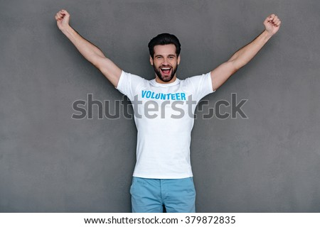Hurray! Cheerful young man in volunteer t-shirt reaching out his armsand looking at camera with smile while standing against grey background