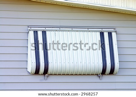 Hurricane protection aluminum shutter installed on tropical home - stock photo